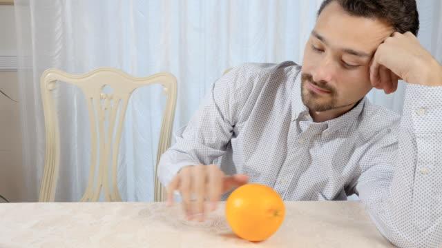 vídeos de stock, filmes e b-roll de homem passa a laranja sobre a mesa - comida feita em casa