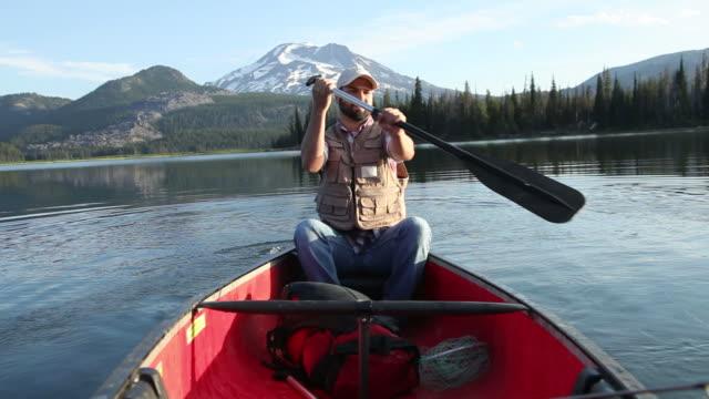 vídeos de stock, filmes e b-roll de homem em canoa de remo - américa do norte
