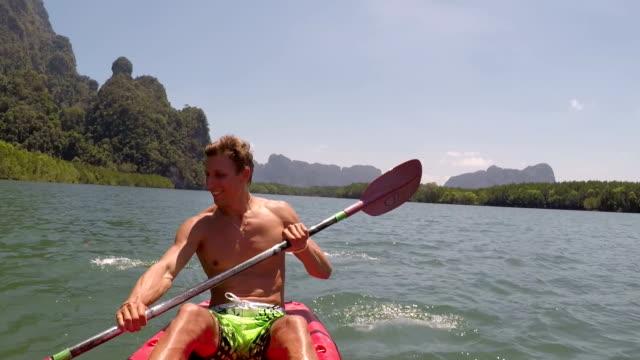 カヤック ボートに乗って美しいラグーン アクション カメラ若い男パドリングの POV でカヤックを漕ぐ男 ビデオ
