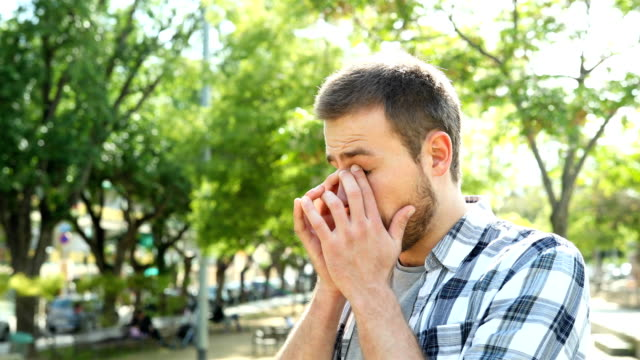 Man rubbing his eyes that sting him due to allergy in a park.mov Man rubbing his eyes that sting him due to allergy or infection in a park season stock videos & royalty-free footage