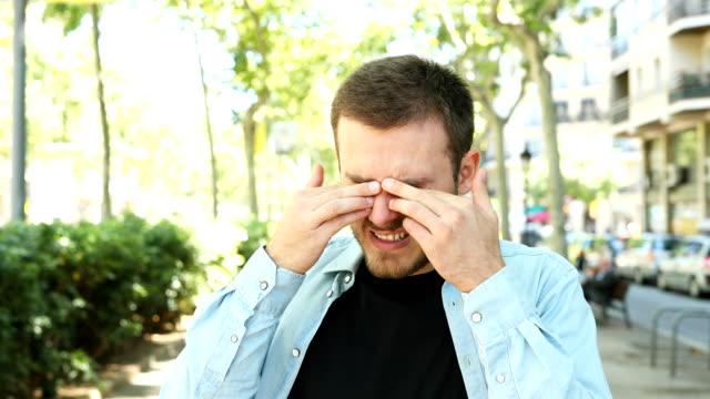 vídeos de stock, filmes e b-roll de homem que esfregam seus olhos que o picam devido à alergia - primavera estação do ano