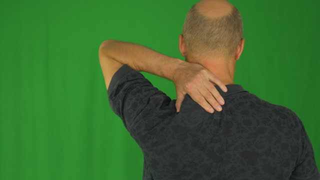 Man rubbing his shoulders with left hand. Back view waist up in polo shirt. video