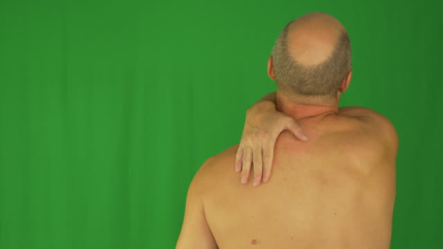 Man rubbing his shoulders with right hand. Back view naked waist up. video
