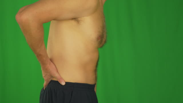 Man rubbing lower back by hands. Side profile view close up. video