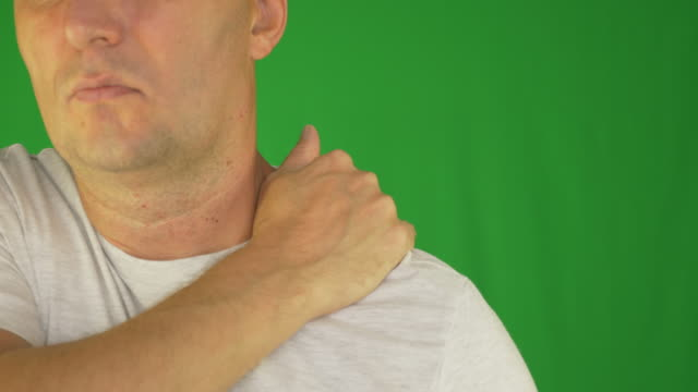 Man rubbing neck and shoulders with hand. Extreme close up front view. Locked shot. video