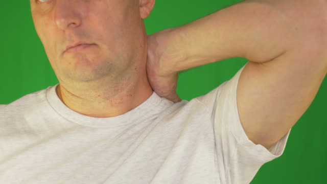Man rubbing neck and shoulders with left hand. Extreme close up front view. Locked shot. video
