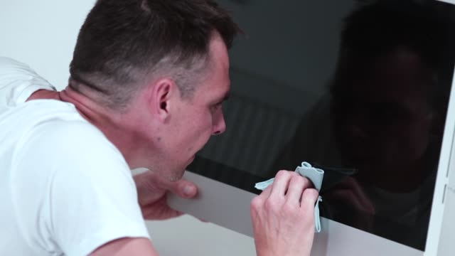 A man rubs the protective glass of the monitor. Removing solid dirt from glass.