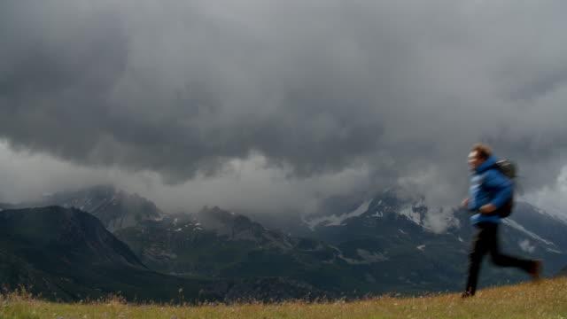 vídeos de stock e filmes b-roll de a man running across a mountain range as stormy weather approaches. - weatherman