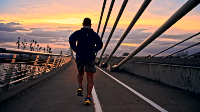 TS Man Running Across The Bridge HD1080p: TRACKING Camera Stabilization shot of a young man jogging across the bridge at dusk. The footage was shot in raw. Also available in 4K resolution. dawn stock videos & royalty-free footage