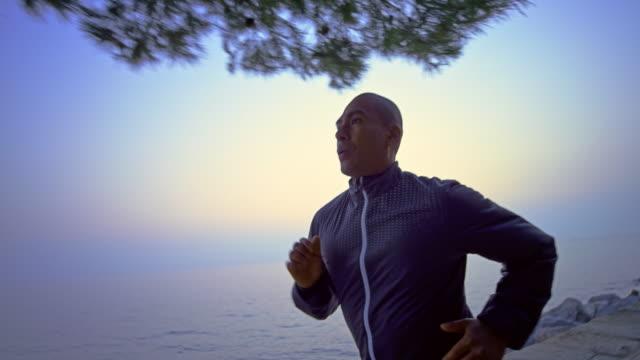 slo mo ts man sisli bir sabah deniz boyunca çalışan - beden bilinçli stok videoları ve detay görüntü çekimi