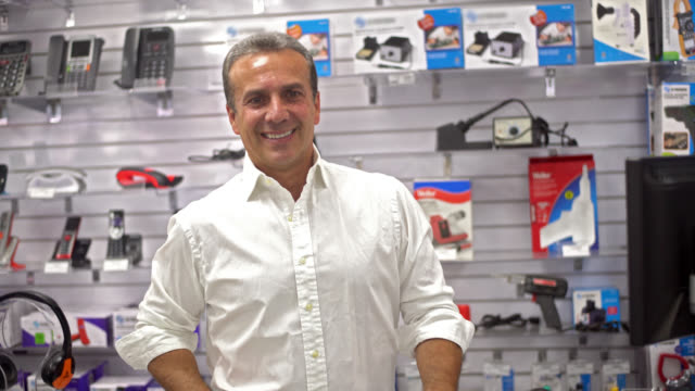 Man running an electronics store Casual man running an electronics store and smiling behind the counter electronics store stock videos & royalty-free footage