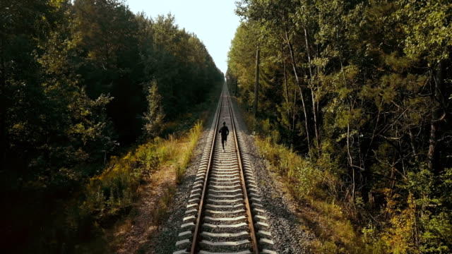Man running between the rail lines. Drone back view. Athlete rushing to new perspective on autumn forest railroad video