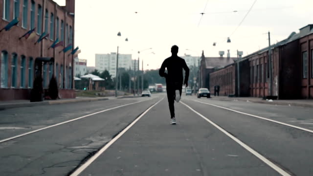 Man running fast in the middle of an old street. Real time shot. Freedom. Camera follows sportsman between tram tracks video