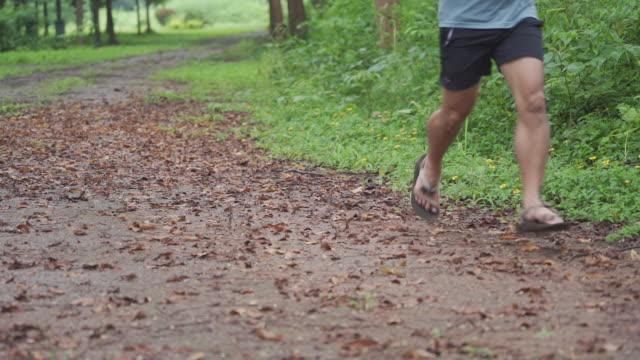 slow mo man ileri koşuyor / kros yolunda kameraya geri koşuyor. - islak stok videoları ve detay görüntü çekimi