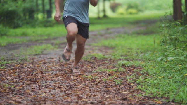 Man running full speed with Minimalist running sandals on cross country road.
