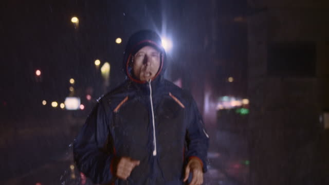 SLO MO Man running in city at night in heavy rain video