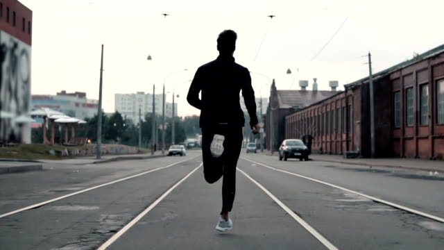 man running in the middle of the street. background shot. slow motion. abstract concept of individual success and fame - sport filmów i materiałów b-roll