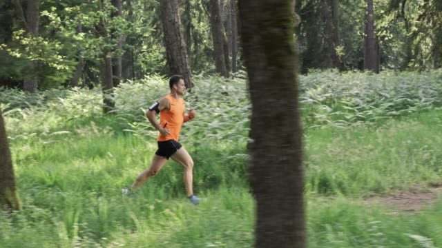SLO MO DS Man running on a forest trail in sunshine Slow motion wide dolly shot of a man in orange t-shirt running on a forest trail while listening to music. tank top stock videos & royalty-free footage