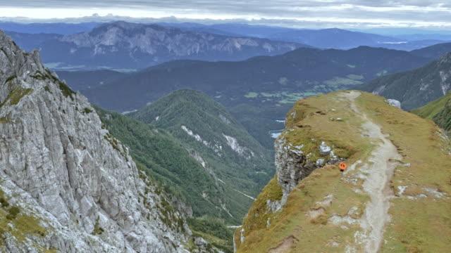 aerial man kör på en bergsrygg som är hög i bergen med utsikt över en vacker dal nedan - endast en medelålders man bildbanksvideor och videomaterial från bakom kulisserna
