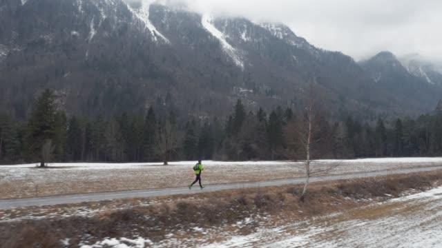 雪の下で冬の谷を越えて道で走っている空中の人に山の頂上が覆われています。 - 日常から抜け出す点の映像素材/bロール