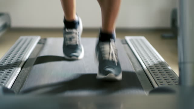 SLO MO CU Man running on a treadmill