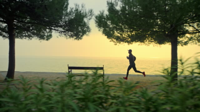 SLO MO Man running on a wide pathway along the sea in sunrise