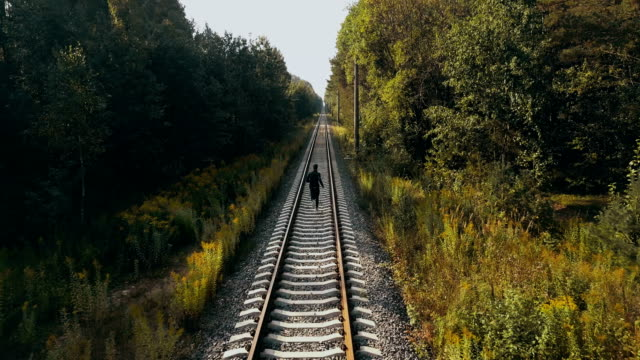 Man running on autumn forest railroad. Drone back view. Athlete on path to clear vision horizon. Cinematic shot video