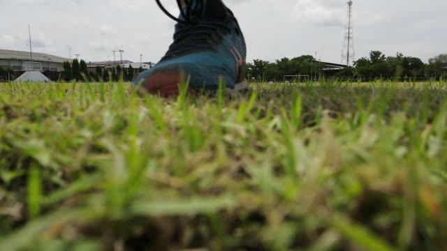 egzersiz yapmak için çimenlikte koşan bir adam. - bir orta yetişkin erkek sadece stok videoları ve detay görüntü çekimi