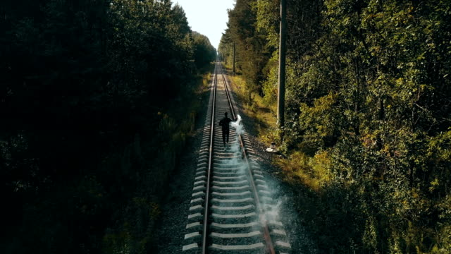 Man running on train tracks with smoke bomb. Drone back view. Runner signaling to oncoming train. Autumn forest railway video