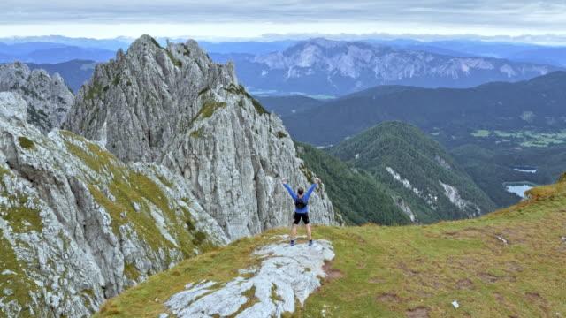 vídeos de stock e filmes b-roll de aerial man running to the mountain edge and raising his hands - dedicação