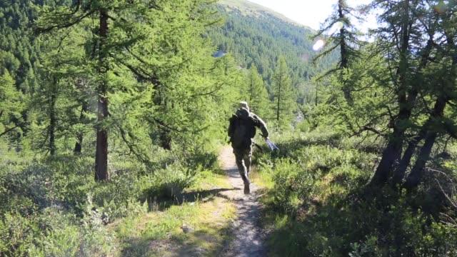 vídeos de stock e filmes b-roll de a man runs away from danger in the forest. - fugir
