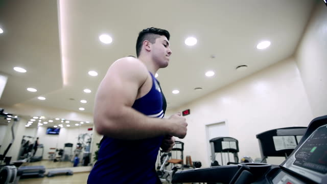 Man runs on a treadmill in the gym video