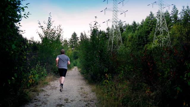 man läuft auf kiesweg im wald in der nähe von stromleitungen - vancouver kanada stock-videos und b-roll-filmmaterial