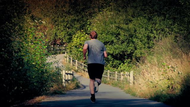 mann läuft weg durch den park - vancouver kanada stock-videos und b-roll-filmmaterial
