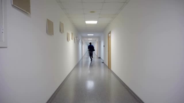 a man runs through a long corridor - сбежавший из дома стоковые видео и кадры b-roll