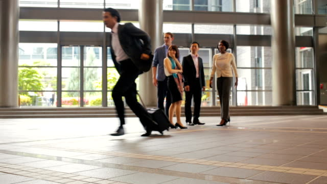 Man Rushes Past Group of Business People in Office Lobby video