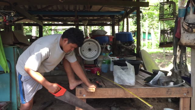 Man sawing a wooden block with a hand saw Man sawing a wooden block with a hand saw handle stock videos & royalty-free footage
