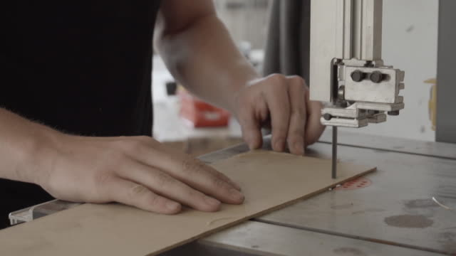 Mann eine Holzplatte mit einer Stichsäge Sägen – Video