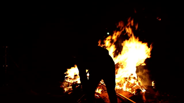 man sawing wood for bonfire (easter fire / Osterfeuer) video