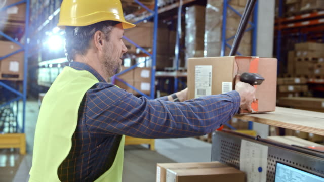 Man scanning the packages on his desk in warehouse with a handheld scanner video