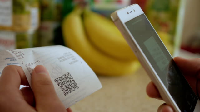 a man scans the qr code on a check from a supermarket. - scontrino fiscale video stock e b–roll