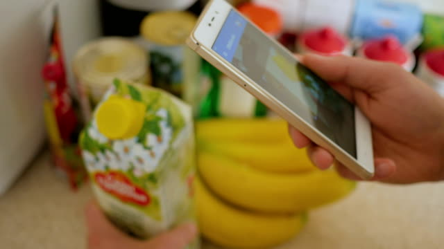 A man scans the QR code on a check on a juice box from a supermarket. video