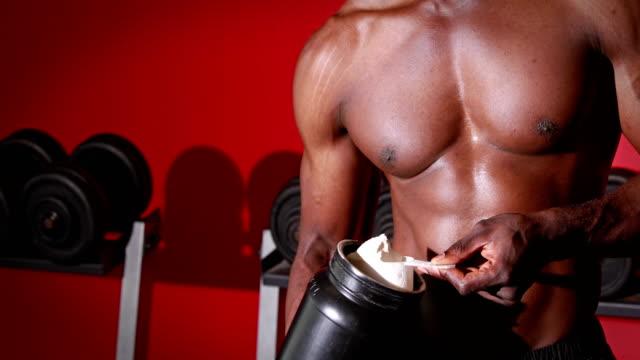 Man scooping protein powder at gym gym video