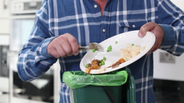 Man Scraping Food Leftovers Into Garbage Bin Man Scraping Food Leftovers Into Garbage Bin food stock videos & royalty-free footage
