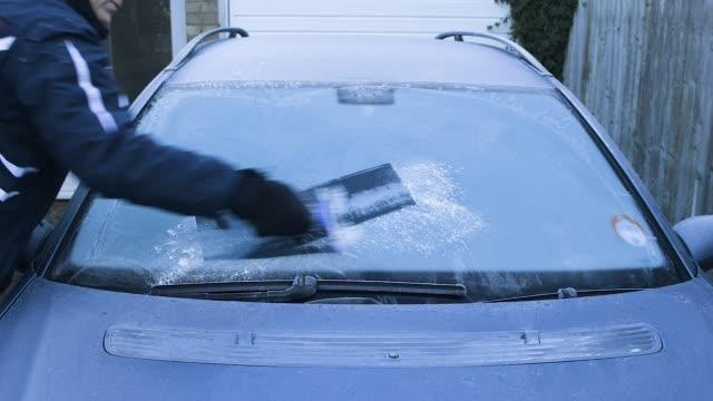man scraping ice from car windscreen. - brina ghiaccio video stock e b–roll