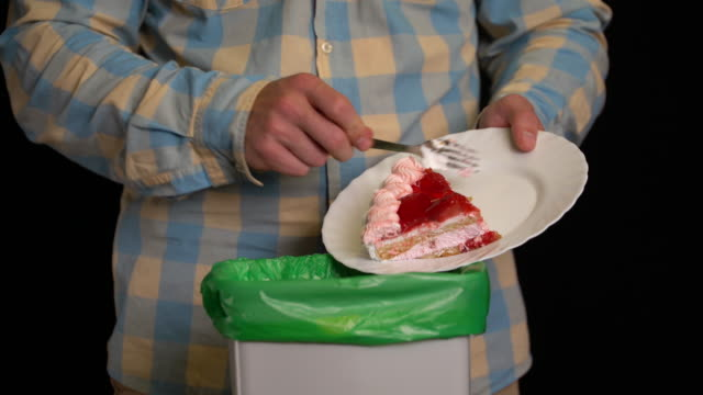 Man scraping with a plate a strawberry cake into garbage bin. Man scraping with a plate a strawberry cake into garbage bin. leftovers stock videos & royalty-free footage