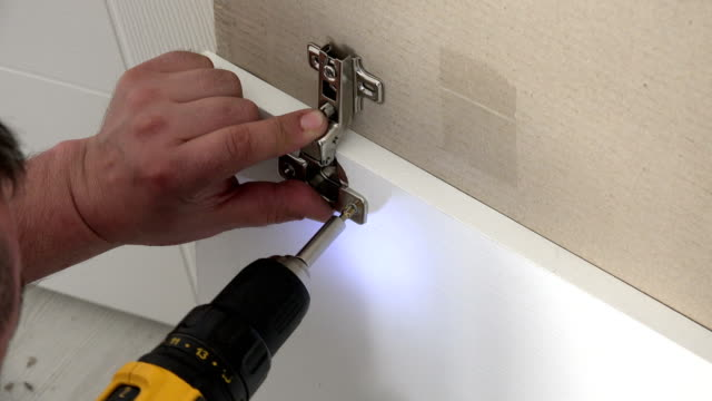 Man screws hinge into cabinet video