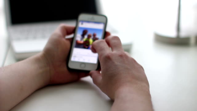Man scrolling a social media site using his smart phone video