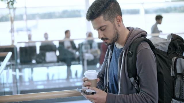 mannen rullning hans telefon samtidigt dricker kaffe och väntar på sin flight på flygplatsen - unga män bildbanksvideor och videomaterial från bakom kulisserna