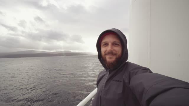 mann selfie video auf dem deck eines schiffes in rauer see - rau stock-videos und b-roll-filmmaterial